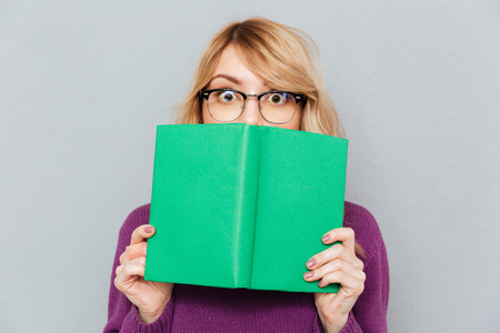 Photo for Woman in glasses hiding face with green book - Royalty Free Image