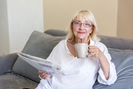 Photo pour Senior woman in eyeglasses holding a newspaper while having a cup of coffee in the morning on a couch a home - image libre de droit