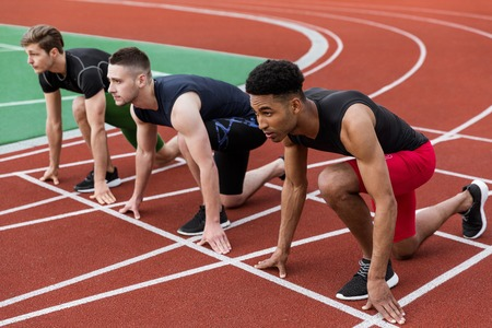 Photo for Image of multiethnic athlete group ready to run on running track outdoors. Looking aside. - Royalty Free Image