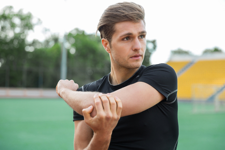 Photo for Picture of young concentrated male athlete make stretching exercises outdoors. Looking aside. - Royalty Free Image
