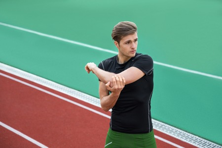 Photo for Image of young concentrated male athlete make stretching exercises outdoors. Looking aside. - Royalty Free Image