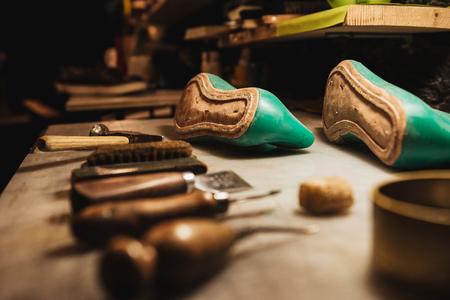 Photo pour Image of shoes and instruments on table at footwear workshop. - image libre de droit