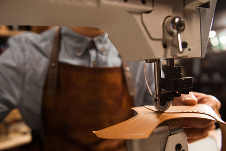 Photo pour Close up of a cobbler using sewing machine at a workshop - image libre de droit