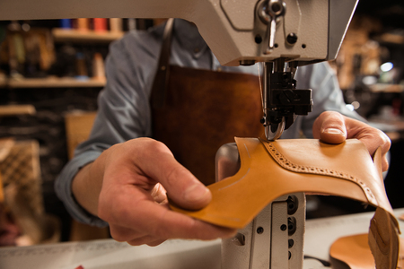 Photo for Man cobbler stitching leather patrs on a sewing machine - Royalty Free Image