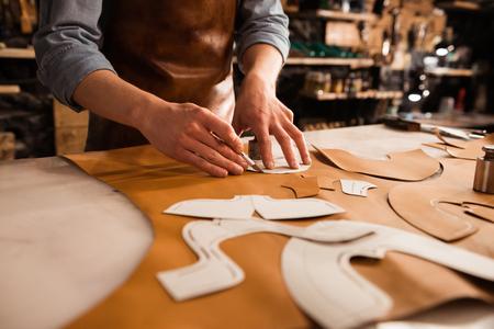 Foto de Close up of a shoemaker measuring and cutting leather in a workshop - Imagen libre de derechos