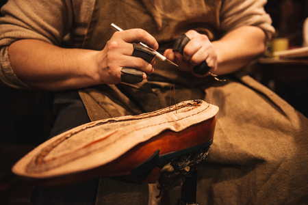 Photo for Cropped photo of young man shoemaker at footwear workshop. - Royalty Free Image