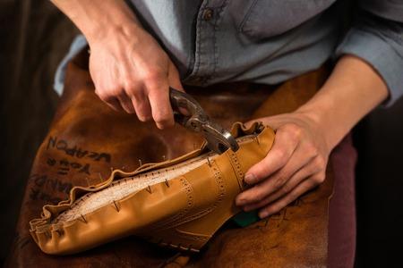 Foto de Cropped photo of shoemaker sitting in workshop making shoes - Imagen libre de derechos