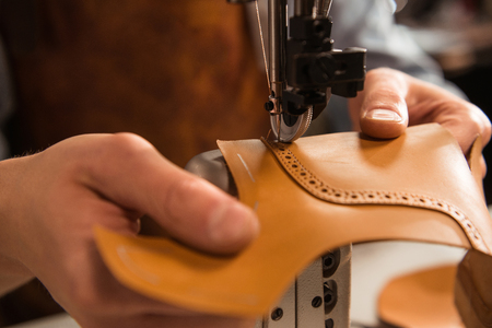 Photo for Close up of a cobbler stitching a part of the shoe at a workshop - Royalty Free Image