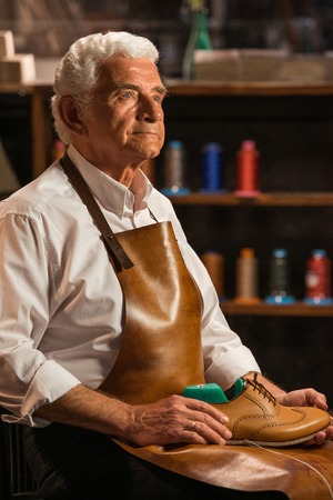 Foto de Image of mature handsome shoemaker in workshop holding shoes. Looking aside. - Imagen libre de derechos