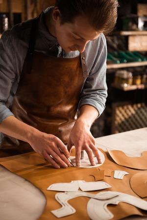 Foto de Close up of a male cobbler working with leather textile at his workplace - Imagen libre de derechos