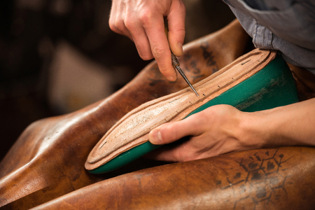 Foto de Cropped image of bootmaker sitting in workshop making shoes - Imagen libre de derechos