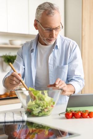 Photo pour Image of handsome concentrated mature man wearing glasses standing at the kitchen cooking salad using tablet computer. Looking aside. - image libre de droit