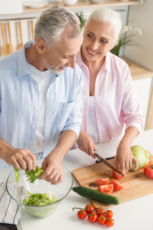 Photo pour Image of happy mature loving couple family standing at the kitchen and cooking salad. Looking aside. - image libre de droit
