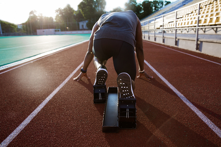 Photo for Back view of a young male athlete at starting block on running track - Royalty Free Image