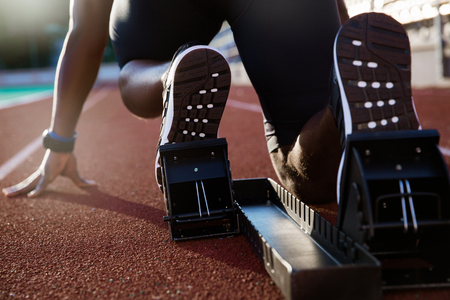 Foto per Back view of men's feet on starting block ready for a sprint start - Immagine Royalty Free