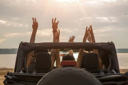 Photo pour Back view of a group of happy friends sitting in a car with hands raised and having fun - image libre de droit