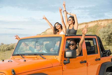 Foto de Group of happy multiethnic friends having fun by travelling together by a car - Imagen libre de derechos