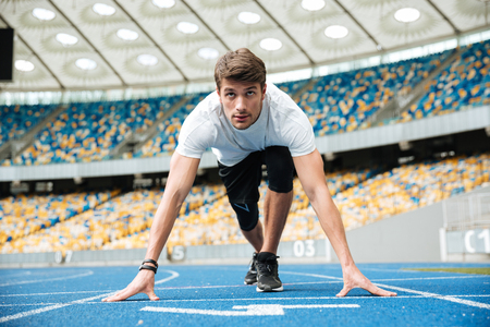Photo for Concentrated sprinter getting ready to start a race at the stadium - Royalty Free Image