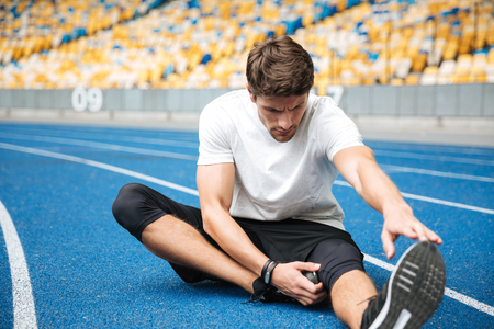 Photo pour Picture of serious young sports man at the stadium outdoors make stretching exercises. - image libre de droit
