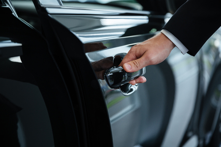 Foto de Close up of a male hand closing a car door at the dealership - Imagen libre de derechos