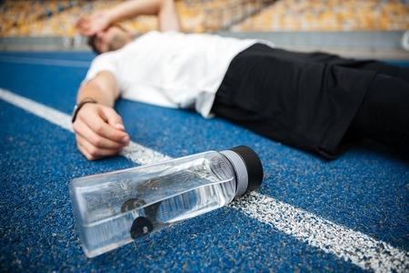 Foto de Exhausted young sportsman lying on a racetrack with bottle of water at the stadium - Imagen libre de derechos