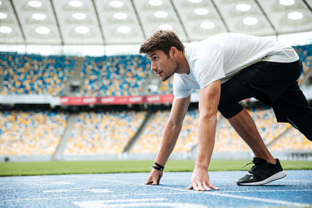 Photo for Side view of a male runner ready for sports exercise on a racetrack at the stadium - Royalty Free Image