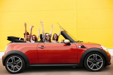 Photo pour Image of happy emotional four young women friends sitting in car outdoors. Looking camera. - image libre de droit