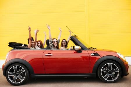 Foto de Image of happy emotional four young women friends sitting in car outdoors. Looking camera. - Imagen libre de derechos