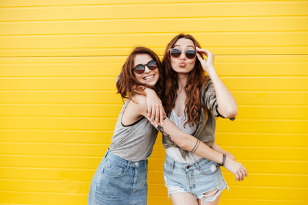 Photo pour Image of two young happy women friends standing over yellow wall. Looking at camera blowing kisses. - image libre de droit