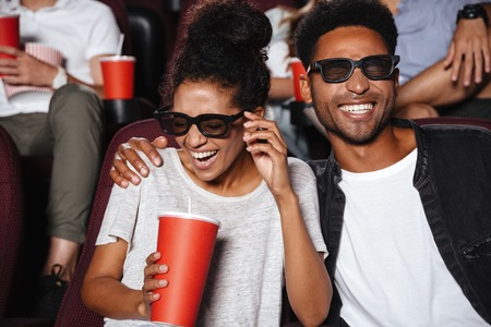 Photo for Attractive afro american couple watching 3D movie and laughing while sitting in a movie theater - Royalty Free Image