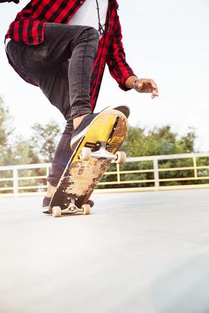 Foto de Photo of young dark skinned guy skateboarding. Against the nature background. - Imagen libre de derechos