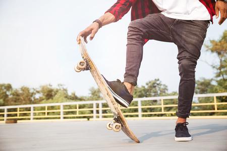 Foto de Cropped photo of young dark skinned man skateboarding. Against the nature background. - Imagen libre de derechos