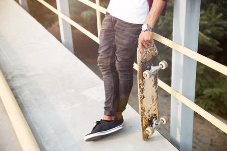 Foto de Cropped poung dark skinned man holding skateboard. Against the nature background. - Imagen libre de derechos