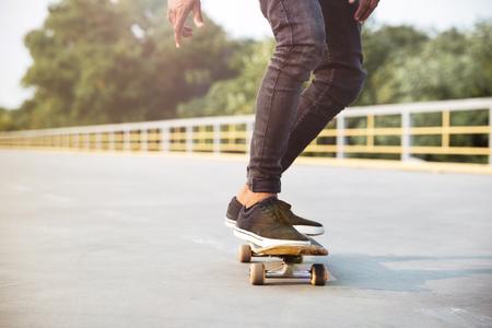 Foto de Photo of young dark skinned man skateboarding. Against the nature background. - Imagen libre de derechos
