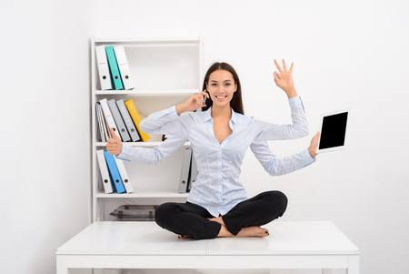 Photo pour Smiling busy successful business woman multitasking in the office while sitting on the table - image libre de droit
