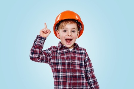 Foto de Small architect boy with helmet pointing up to copy space and smiling isolated on blue background - Imagen libre de derechos