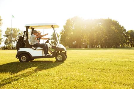 Photo pour Two male golfers driving in a golf cart along green course - image libre de droit