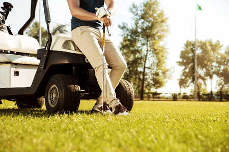 Photo for Cropped image of a male golfer leaning on a cart and holding golf club outdoors - Royalty Free Image