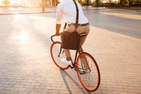 Foto de Cropped picture of handsome young african man early morning with bicycle walking outdoors. - Imagen libre de derechos