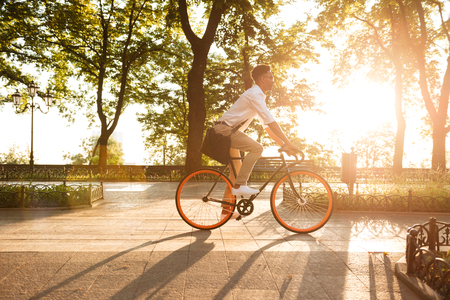 Foto de Image of young african man early morning with bicycle walking outdoors. Looking aside. - Imagen libre de derechos