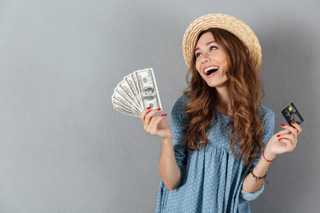 Photo for Photo of happy young pretty woman standing over grey wall wearing hat holding money and credit card. - Royalty Free Image