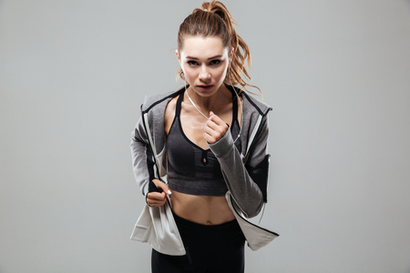 Photo pour Concentrated fitness woman in sportswear listening to music with earphones while running isolated over gray background - image libre de droit