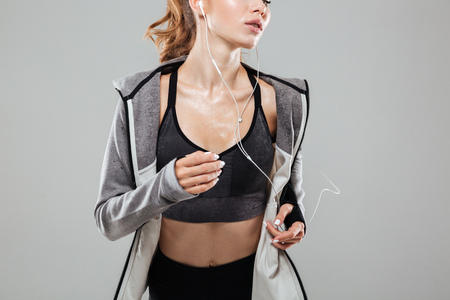 Photo pour Cropped image of a sweaty fitness woman in sportswear listening to music with earphones while running isolated over gray background - image libre de droit