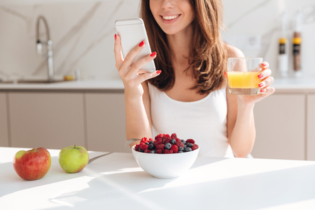 Foto de Cropped image of smiling pretty woman looking at mobile phone and holding glass of orange juice while having breakfast in a kitchen - Imagen libre de derechos