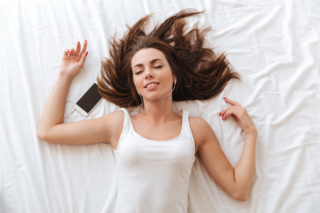 Photo for Top view of a happy woman enjoys listening to music with earphones while laying on bed at home - Royalty Free Image