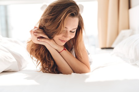 Photo pour Portrait of brunette carefree woman lying in bed and smiling in the morning - image libre de droit