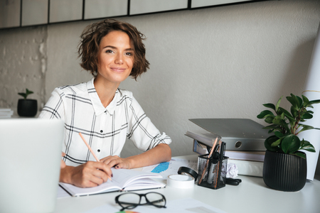 Foto de Smiling pretty woman working by the table in co working office and looking at the camera - Imagen libre de derechos