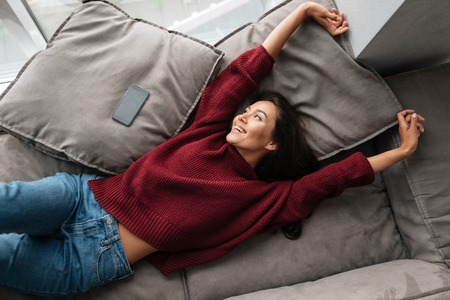Photo for Top view of a smiling beautiful asian woman in sweater lying on a couch at home with blank screen mobile phone and stretching hands - Royalty Free Image