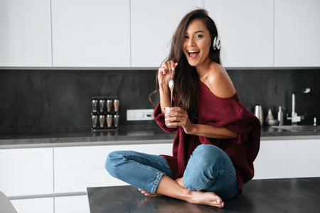 Photo pour Happy young asian woman in headphones eating dessert with a spoon from a jar in a kitchen - image libre de droit