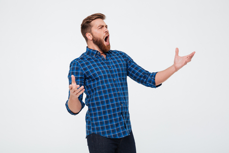 Photo for Young attractive bearded man singing loud while standing isolated over white background - Royalty Free Image